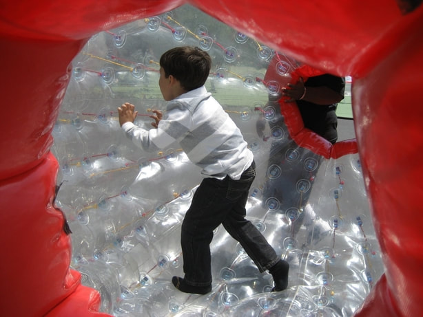 Young boy walking inside large blow up ball known as a hamster ball