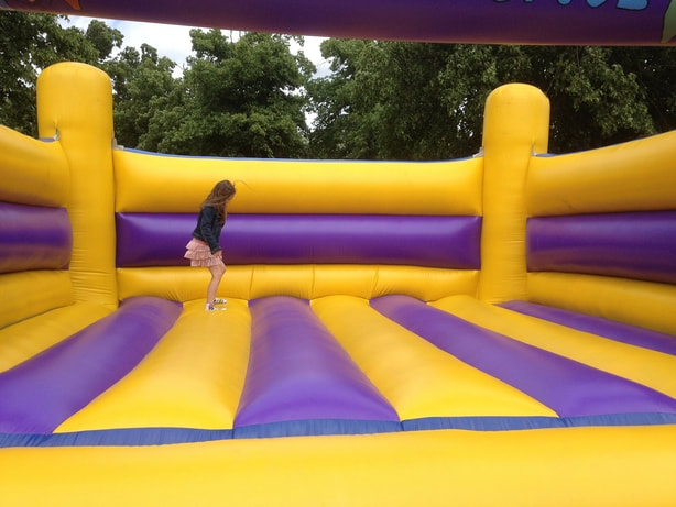 young girl jumping by herself in a bouncy castle