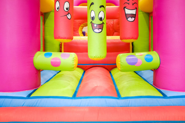 bright and colorful obstacle course with faces on extruding blow up figures