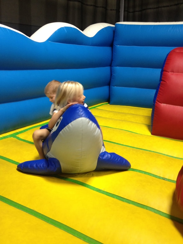 Two children riding a whale in a bouncy house