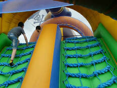 Young child climbing up a bouncy castle climbing wall