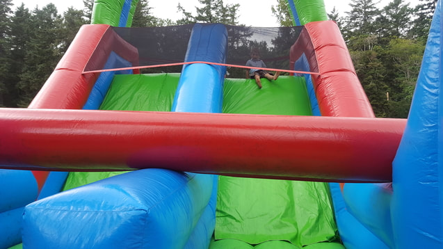 Young boy at the top of small double blow up slide