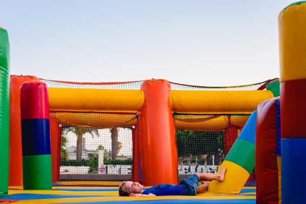 young boy laying down in a bouncy castle obstacle course