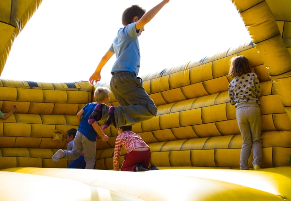 children playing in a yellow brick bouncy castle while one boy jumps